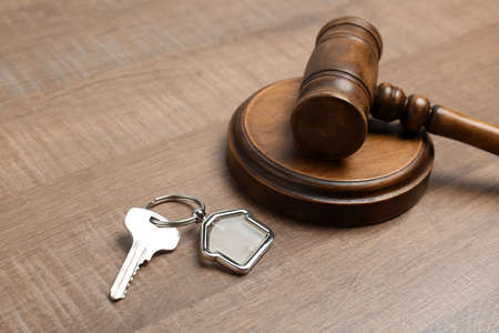 Judge gavel and house key on wooden background. Estate law concept