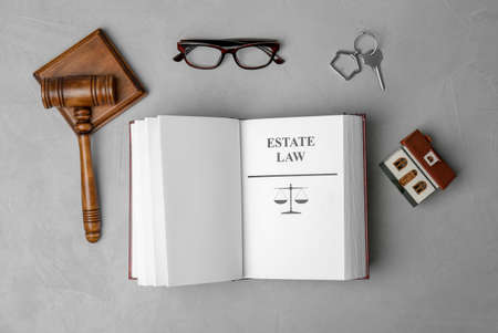 Flat lay composition with book, gavel and house model on grey background. Estate law concept