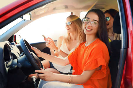 Happy beautiful young women together in car