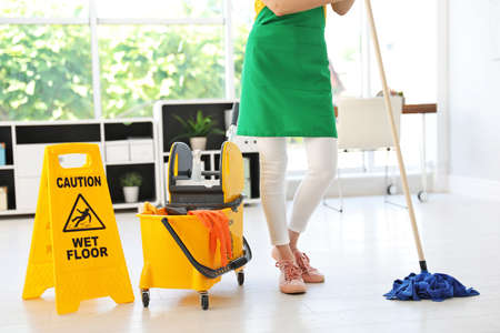 Young woman with mop and bucket cleaning office