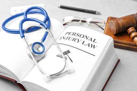 Book with words PERSONAL INJURY LAW and stethoscope on table Stock Photo