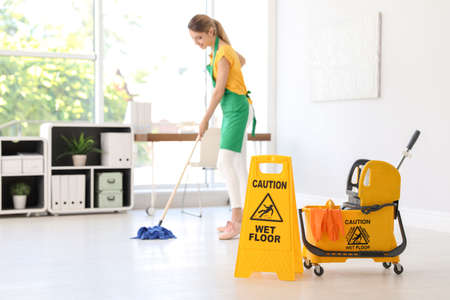 Phrase CAUTION WET FLOOR on safety sign, mop bucket with cleaning supplies and young woman on background