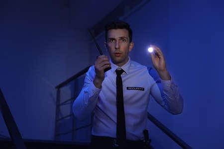 guardia de seguridad masculino con la linterna y la tecnología de transmisor de electricidad en la habitación oscura