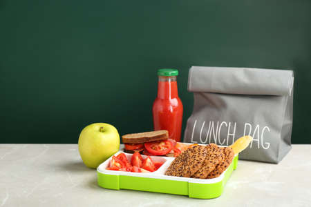 Lunch box with appetizing food and bag on table near chalkboard