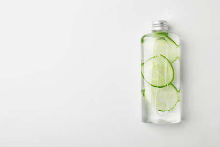 Bottle with cucumber water on white background, top view. Fresh skin care tonic