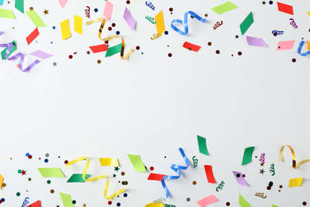 Colorful confetti and streamers on white background, top view