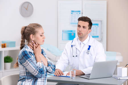 Coughing young woman visiting doctor at clinic