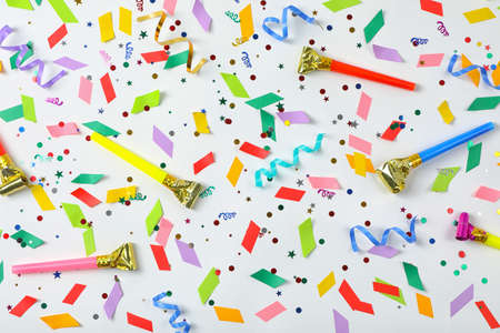 Colorful confetti, streamers and party blowers on white background, top view