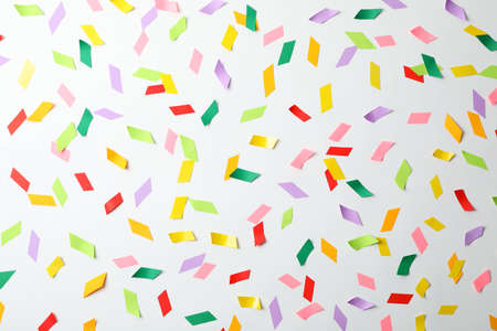Colorful confetti on white background, top view