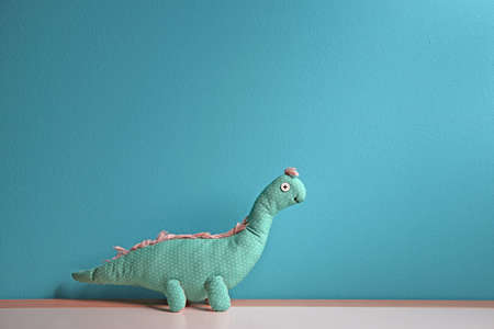 Abandoned toy dinosaur on table against color background. Time to visit child psychologist Stock Photo