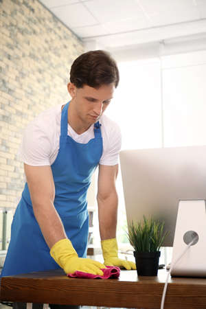 Young man in apron and gloves cleaning office