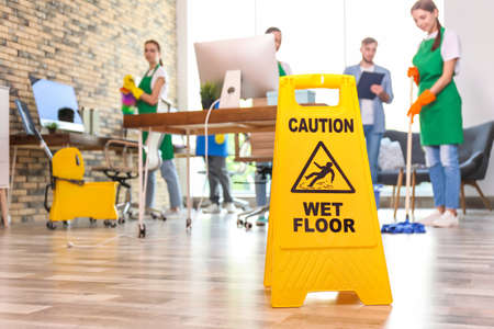 WET FLOOR sign and team of professional janitors in office
