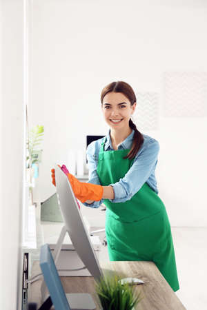 Young woman in apron and gloves cleaning office Stock Photo