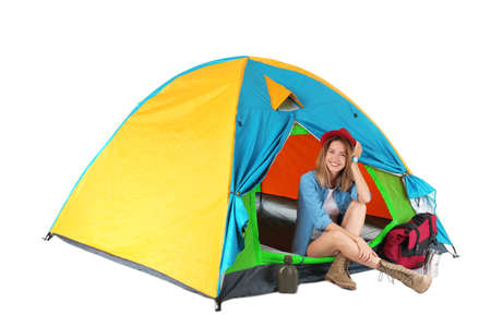 Young beautiful woman sitting in tourist tent on white background