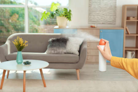 Woman spraying air freshener at home