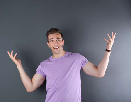 Handsome emotional young man on color background Stock Photo