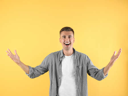Handsome emotional young man on color background Reklamní fotografie