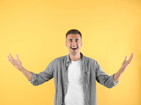 Handsome emotional young man on color background Stock fotó
