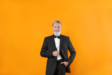 Handsome bearded mature man in suit on color background Stock fotó