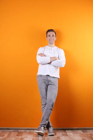 Handsome young man smiling on color background Stock fotó