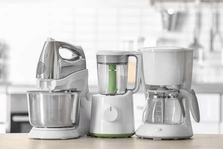 Kitchen appliances on table against blurred background Foto de archivo