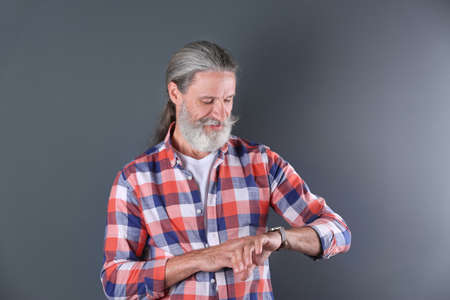 Handsome bearded mature man on color background