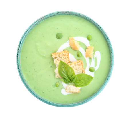 Green pea soup with croutons in bowl on white background, top view