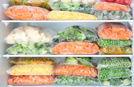 Plastic bags with deep frozen vegetables in refrigerator Stockfoto