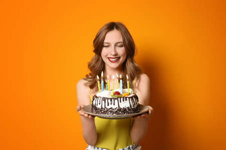 Young woman with birthday cake on color background Archivio Fotografico - 106384532