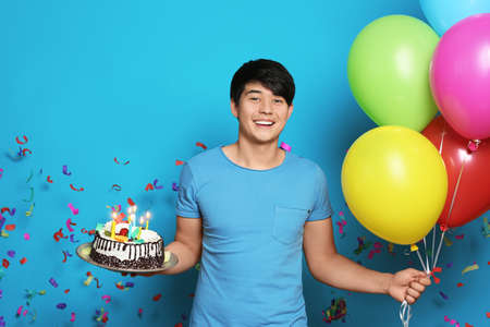 Young man with birthday cake and bright balloons on color background 版權商用圖片