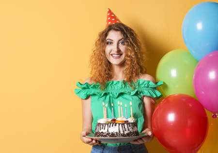 Young woman with birthday cake near bright balloons on color background