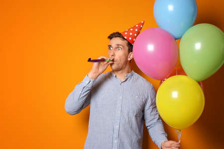 Young man with bright balloons and party blower on color background. Birthday celebration Stock Photo
