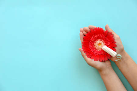 Woman holding flower and tampon on color background, top view. Gynecological care