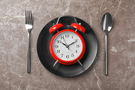 Flat lay composition with alarm clock, plate and utensils on grey background