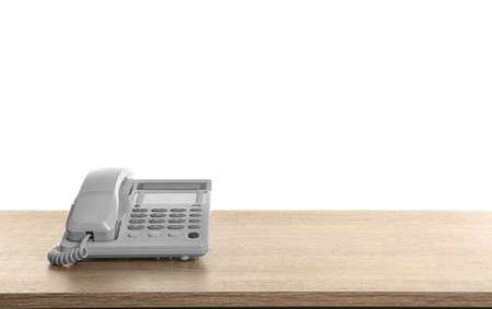 Telephone on wooden table against white background 版權商用圖片