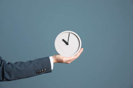 Young businesswoman holding clock on color background. Time management