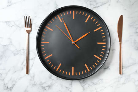 Flat lay composition with clock and utensils on marble background. Time management