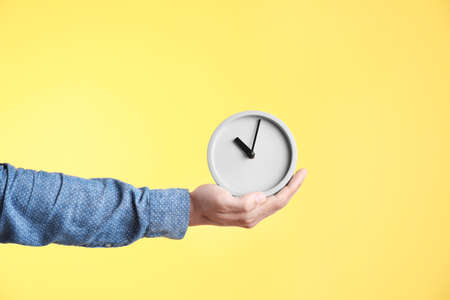 Young man holding clock on color background. Time management