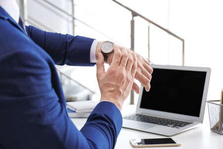 Junger Geschäftsmann, der Zeit auf seiner Armbanduhr am Arbeitsplatz prüft. Zeiteinteilung