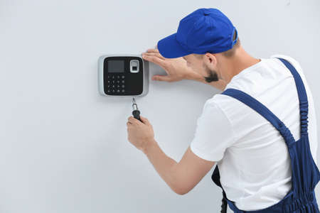 Young male technician installing alarm system indoors