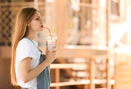 Young woman with cup of delicious milk shake outdoors Banco de Imagens