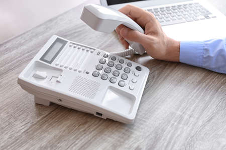 Man picking up telephone at table in office