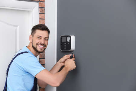 Male technician installing alarm system indoors