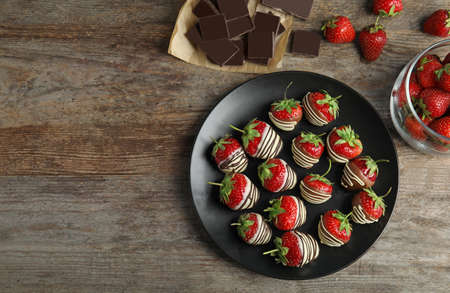 Flat lay composition with chocolate covered strawberries on wooden background