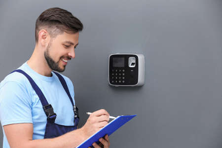 Male technician with clipboard near installed alarm system indoors Stockfoto