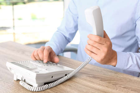 Man dialing number on telephone at workplace Stock Photo