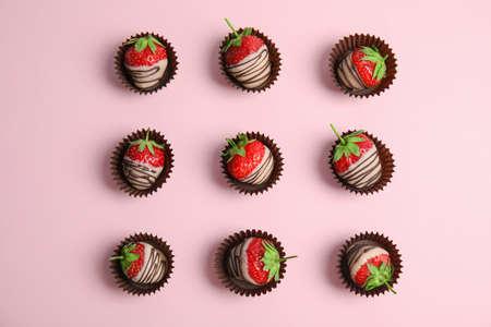 Composizione piatta laica con fragole ricoperte di cioccolato su sfondo colorato