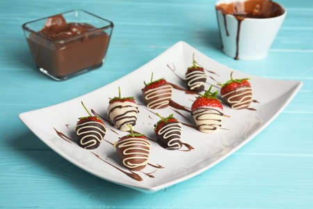 Plate with chocolate covered strawberries on table