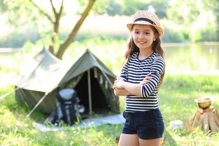 Little girl near tent outdoors. Summer camp