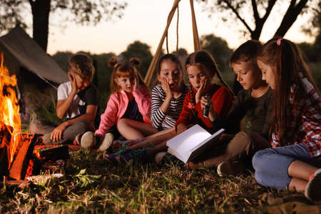 Little children reading book with flashlight outdoors. Summer camp